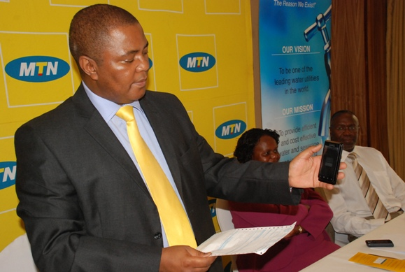 MTN CEO Themba Khumalo demonstrates how to pay water bills using MTN Mobile Money. Looking on far right is NWSC MD Dr. Richard Muhairwe