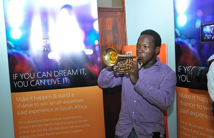Justin Ojago tests the trumpet he won in the Microsoft Make it Happen campaign
