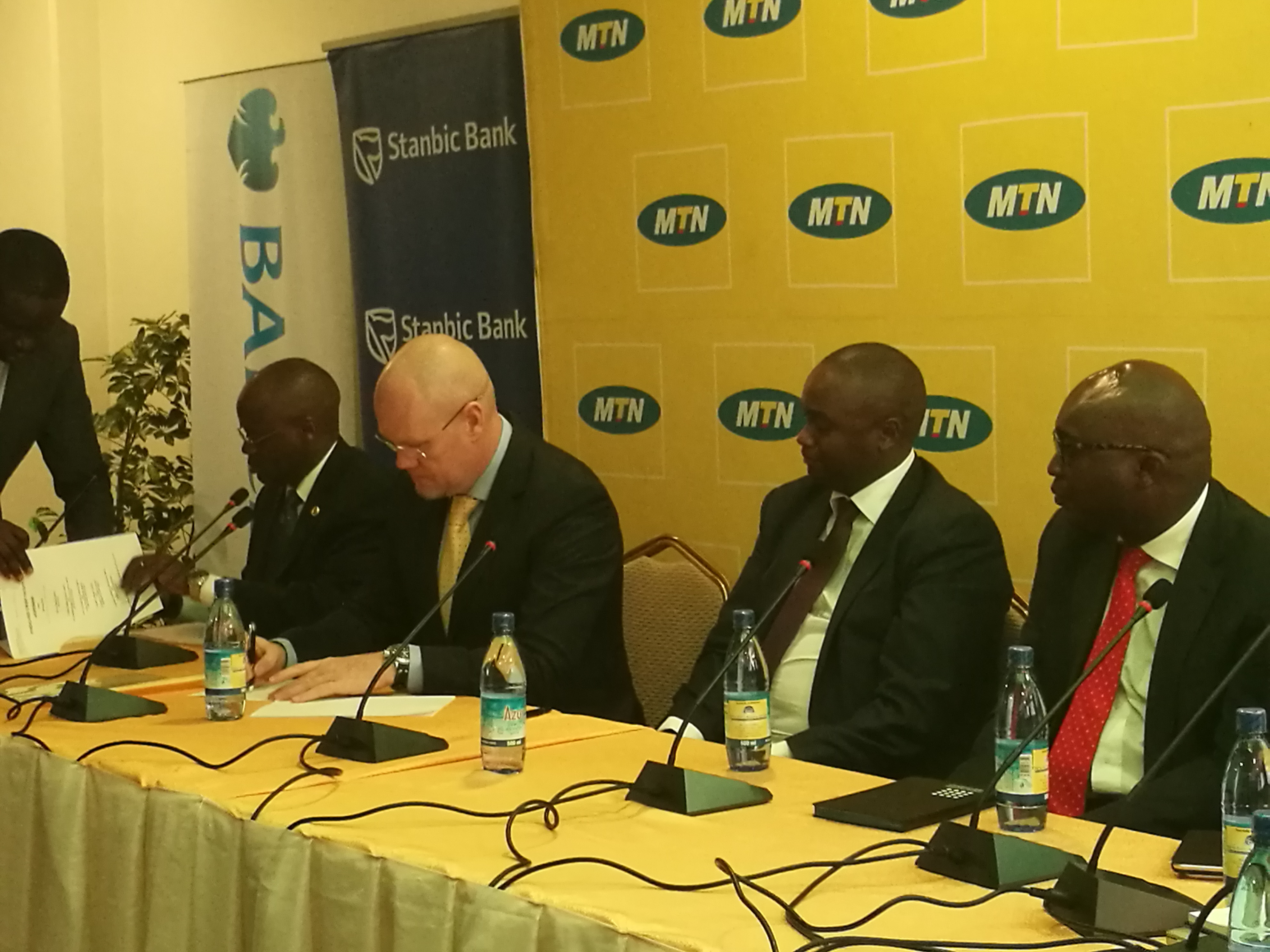 MTN CEO Brian Gouldie 2nd left signs the paperwork for the syndicated credit facility as Stanbic Bank Uganda Patrick Mweheire 3rd left looks on
