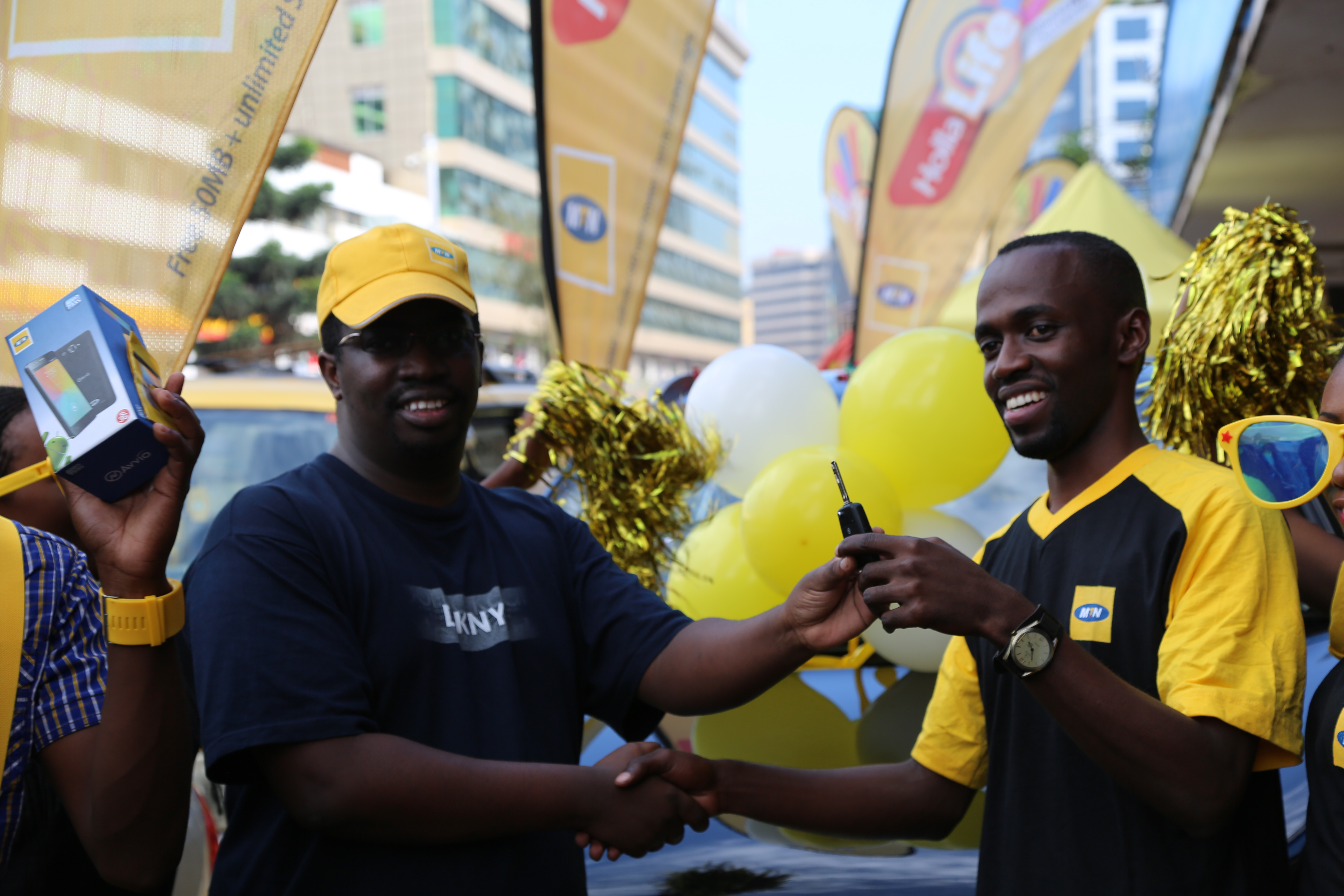 "MTN's Segment Manager Moses Musiime ( R )handing over the car key to Ben Namanya ( L ) 3rd year student from Makerere University after winning in the ongoing Data Campaign of ""Buy, Win and drive a car"". This happened today 12th November 2015 at Simba Telecom on Kampala Road."