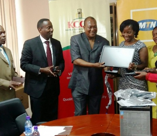 South African High Commissioner to Uganda Prof. Maj. Gen. (Rtd) L. S. Mollo, also trustee member of MTN Foundation hands over computer to Ms. Jennifer Musisi as MTN's Geneal Manager Corporate Services Anthony Katamba looks on.