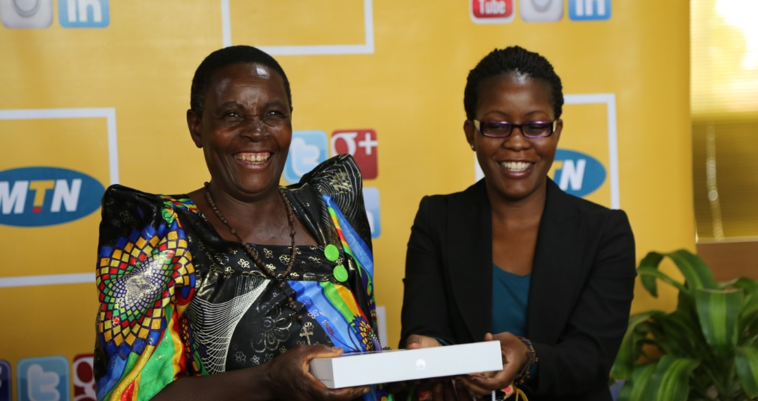 Korubare Fulugyensiyo an excited David Lutalo fan from Isingiro receives a Tablet from MTN's Retention and social media manager Susan Kayemba at Nyonyi Gardens Kololo.
