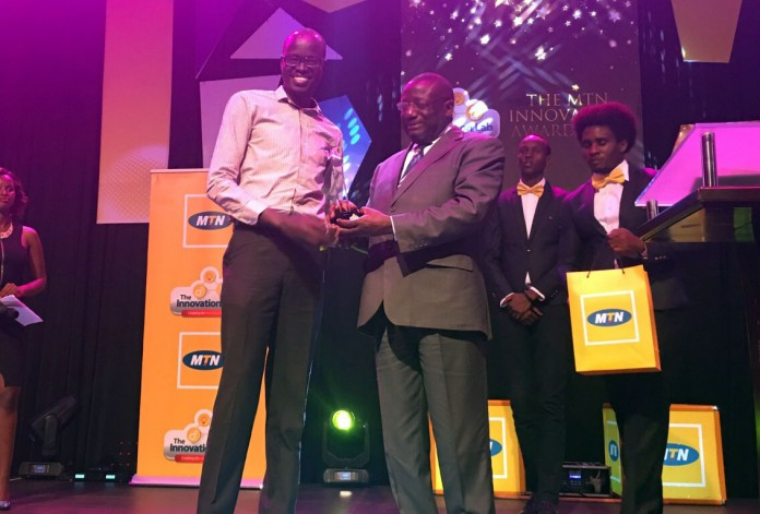 Solomon King receives his award from the guest of honor, ICT Minister Hon Nyombi Thembo.