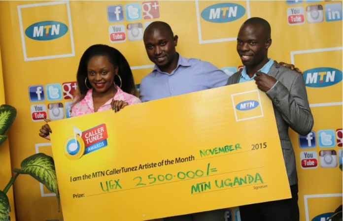 "MTN's Brand Manager Isaac Tegule (Center ) hands over a dummy check of Ugx 2.5M to Chris Evans (Right ) and Rema Namakula (Left) for winning as artists of November in the MTN CRBT Online awards with their duet ""Linda"""