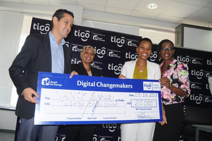 Tigo Tanzania Managing Director, Diego Gutierrez (right), hands over a dummy cheque to Nancy Sumari, (right, in white), one of the winners of the Tigo Digital Change-makers' awards in Dar es Salaam last Thursday. Looking on are, Tigo Corporate Social Responsibility Manager, Halima Okash, (center) and Reach for Change Country Manager, Josephine Msambichaka (Photo Courtesy: Tigo)