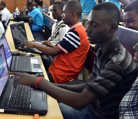 """TO GO WITH AFP STORY BY PIERRE DONADIEU People participate in the 48-hour """"hackathon"""" event, in which seven teams compete to develop innovative applications to facilitate access to information in Africa, at the Ecole Superieure Africaine des Technologies et des Communications in Abidjan on April 18, 2015. In Ivory Coast, only 200,000 out of 23 million inhabitants have an internet subscription, according to the government. The goal of the """"hackathon"""" is """"to identify and support projects that will allow better access to information in African countries"""", a co-organizer of the event said. AFP PHOTO / ISSOUF SANOGO (Photo credit should read ISSOUF SANOGO/AFP/Getty Images)"""