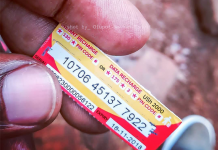 A customer seen holding a scratch/airtime card of UGX2,000 from Airtel Uganda. The scratch/airtime cards are to be terminated for customers to resort to using electronic payments to purchase their cards.