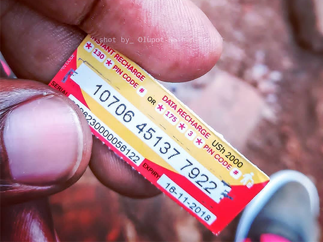 Airtime scratch cards are rumored to be terminated effective July 1st, 2018. Pictured a customer shows off an Airtime 2000 UGX scratch card.