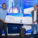 Ogwal Joseph; Founder and Chief Executive (Left), and Watson Atwine (Right); IT Specialist who represented the team, recivce their victory dummy air ticket at the Seedstar Kampala competition at Outbox Hub on Friday 24th, August 2018.