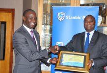 Stanbic Bank Uganda Chief Executive; Patrick Mweheire (right), receives Tax Appreciation Award from (left) Patrick Mukiibi, Ag. Commissioner General at Uganda Revenue Authority.