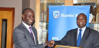 Stanbic Bank Uganda Chief Executive; Patrick Mweheire (right), receives Tax Appreciation Award from (left) Patrick Mukiibi, Ag. Commissioner General at Uganda Revenue Authority.