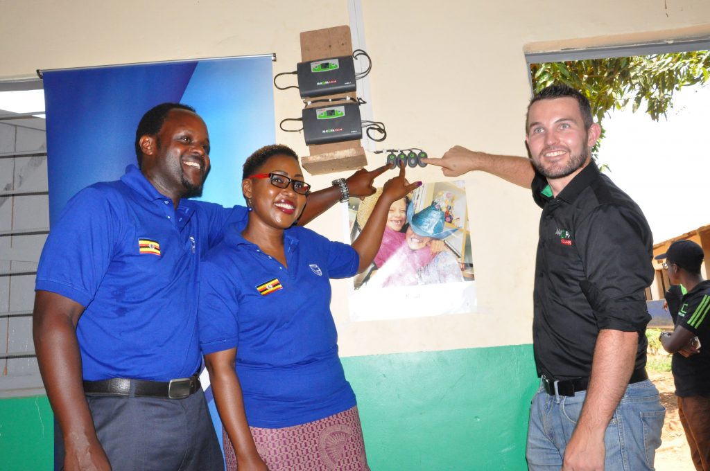 (L-R) Stanbic Sector Head, Power & Infrastructure Henry Kamuntu, Stanbic Head of CSI Barbara Kasekende and M-Kopa Managing Director David Damberger pose for a picture while flipping on the switch for the solar bulbs installed in the Ssenene Primary School library.