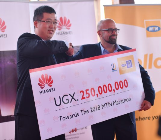 Huawei Uganda Managing Director Mr. Liujiawei hand over a dummy cheque board of Huawei's Contribution to the MTN Marathon of 250,000,000 Ugx to MTN Uganda Chief Marketing Officer Mr. Olivier Pentout.
