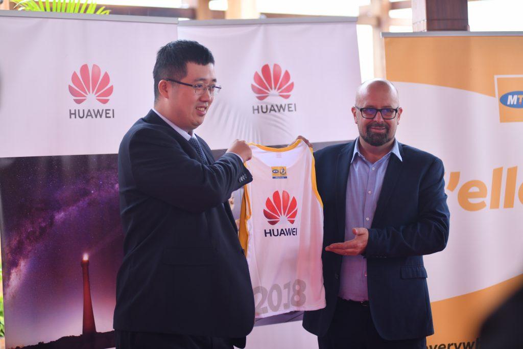 MTN Chief Marketing Officer Mr. Olivier Pentout handing over an MTN Marathon Kit to Huawei Uganda Managing Director Mr. Liujiawei.