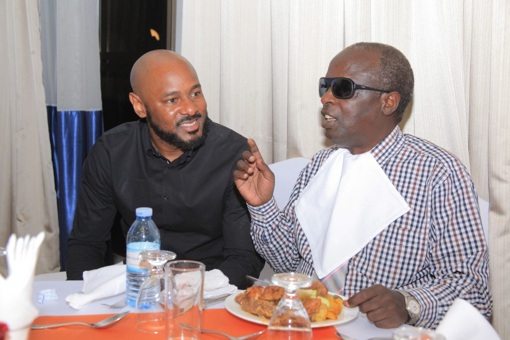 Mr Benoni Okwenje (L), the Chairman ACI Uganda interact with Mr Francis Kinubi (R), the Salama School of the Blind Co-founder and Headmaster during the launch of the association CSR initiative towards the school.