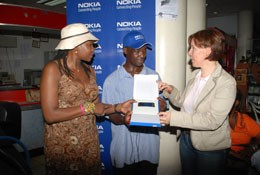 Robert Kituuka (centre) recieves a the Nokia N8 from Nokia Officials during the Take Back and Recycle drive at Uchumi on 20th - 21st November 2010