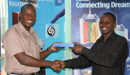 Nokia Sales Manager Mark Mitsumi hands over the phone to Joshua Twinamsiko