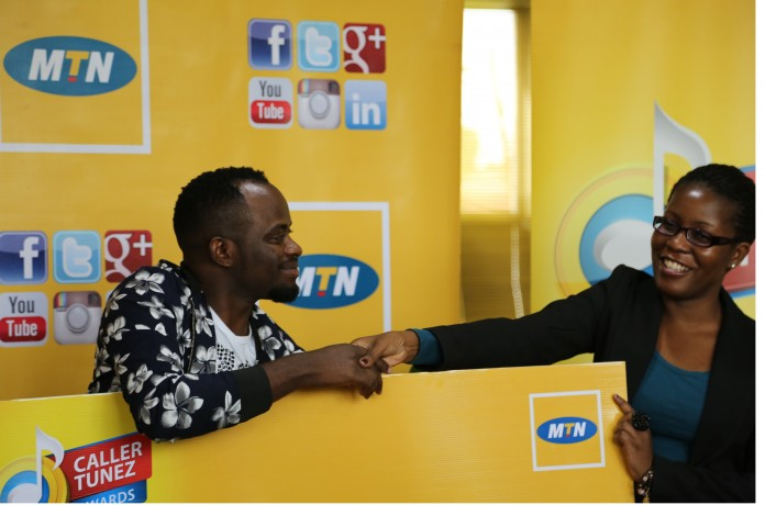 MTN's Retention and Social Media Manager Susan Kayemba hands a Dummy Cheque to David Lutalo at the MTN CRBT Awards prize handover held at MTN Nyonyi gardens