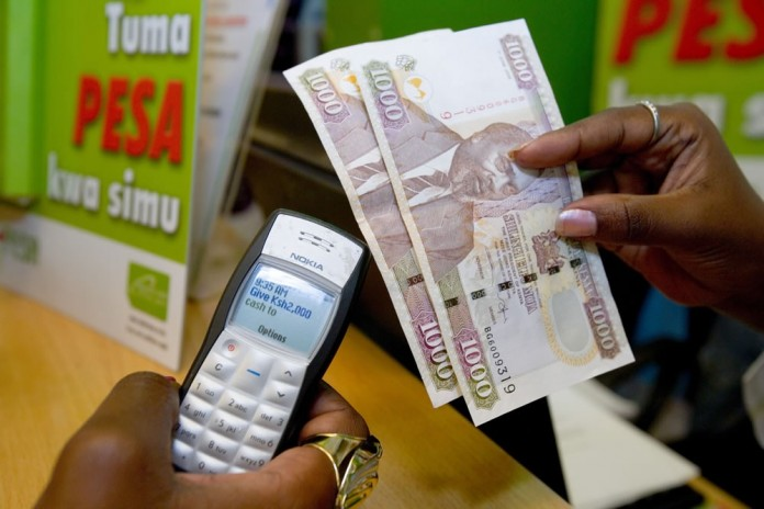 A client in Kenya withdrawing 2000 Ksh from a M-Pesa Agent. Safaricom and MTN Uganda on Monday signed a partnership deal allowing money transfers on their networks. Image Credit: Pritamkabe