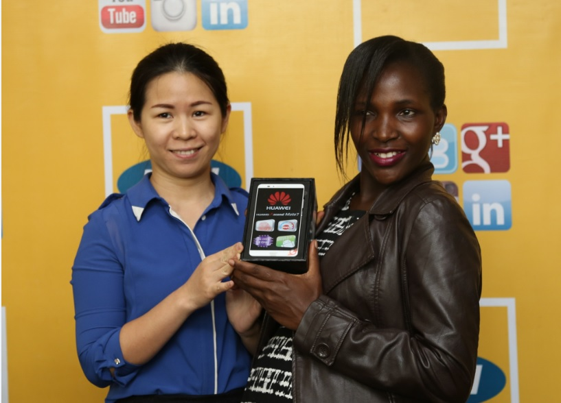 Huawei Digital Service Operations Manager Monicah Yimin Yang (Left ) hands over a Huawei Mate 7 smartphone to Mbabazi Racheal (Right ) as the customer of the Month of November in the MTN CRBT online awards today at MTN Nyonyi Gardens offices.