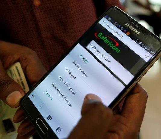 An employee assists a customer to set-up M-Pesa money transfer servive (mobile money) on his handset inside a mobile phone care centre operated by Kenyan's telecom operator Safaricom; in the central business district of Kenya's capital Nairobi, May 11, 2016. REUTERS/Thomas Mukoya - RTX2DU5V