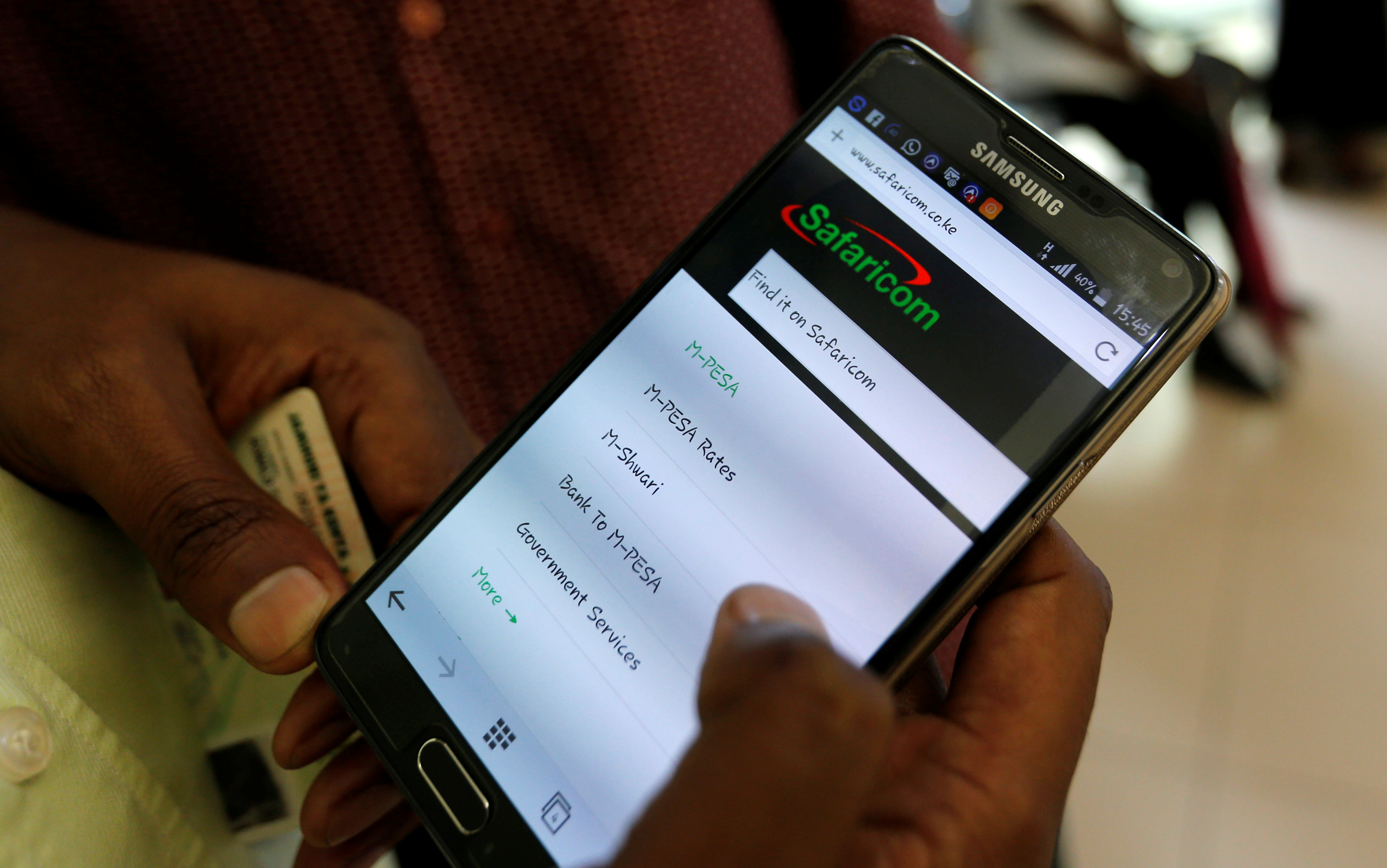 An Employee Ists A Customer To Set Up M Pesa Money Transfer Servive