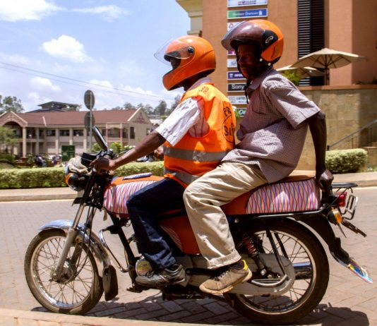 Pioneer moto-taxi ride hailing firm; SafeBoda has been in the business since 2014. A rider is seen wearing a reflective jacket, and helmet carrying an extra one passenger who does have a helmet as well.(Photo Credit: Technology Review)