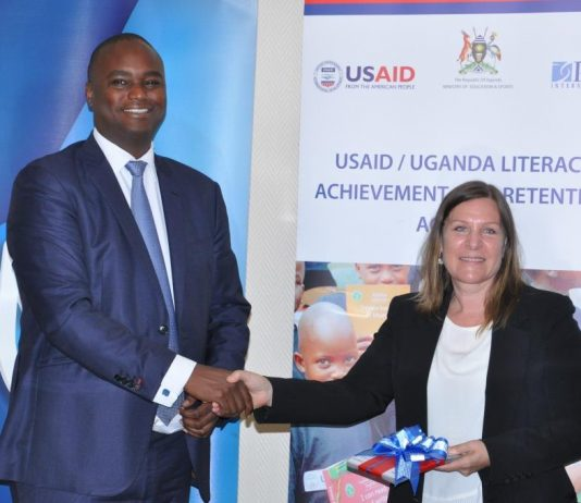 Stanbic Bank Uganda CEO Patrick Mweheire officially handsover reading cards worth Ugx20million to USAID Chief of Party Geri Burkholder.