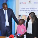Stanbic Bank Uganda CEO Patrick Mweheire and USAID Chief of Party Geri Burkholder officially handover reading cards to Kenneth Kivumbi a P.3 pupil from Bamusuta Primary School, one of the beneficiaries of the cards in Kiboga district.