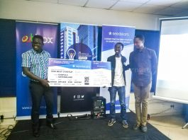 Ogwal Joseph; Founder and Chief Executive (Left), andWatson Atwine (Right; IT Specialist who represented the team, recivce their victory dummy air ticket from Herve Kubwimana, Innovation Facilitator at Merck, at the Seedstar Kampala competition at Outbox Hub on Friday 24th, August 2018.