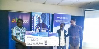 Ogwal Joseph; Founder and Chief Executive (Left), and Watson Atwine (Right; IT Specialist who represented the team, recivce their victory dummy air ticket from Herve Kubwimana, Innovation Facilitator at Merck, at the Seedstar Kampala competition at Outbox Hub on Friday 24th, August 2018.