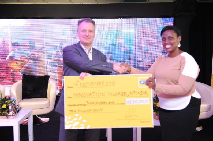 Wim Vanhelleputte CEO MTN Uganda (L) handsover a UGX310 million cheque to The Innovation Village as part of partnership that will see the telecom provide high speed internet and server for technology hub.