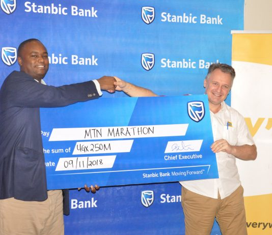 Patrick Mweheire, Stanbic Bank's CEO (L) hands over the banks contribution of UGX250M to MTN Uganda's CEO Mr. Wim Vanhelleputte. The contribution goes towards improving maternal health in Uganda.