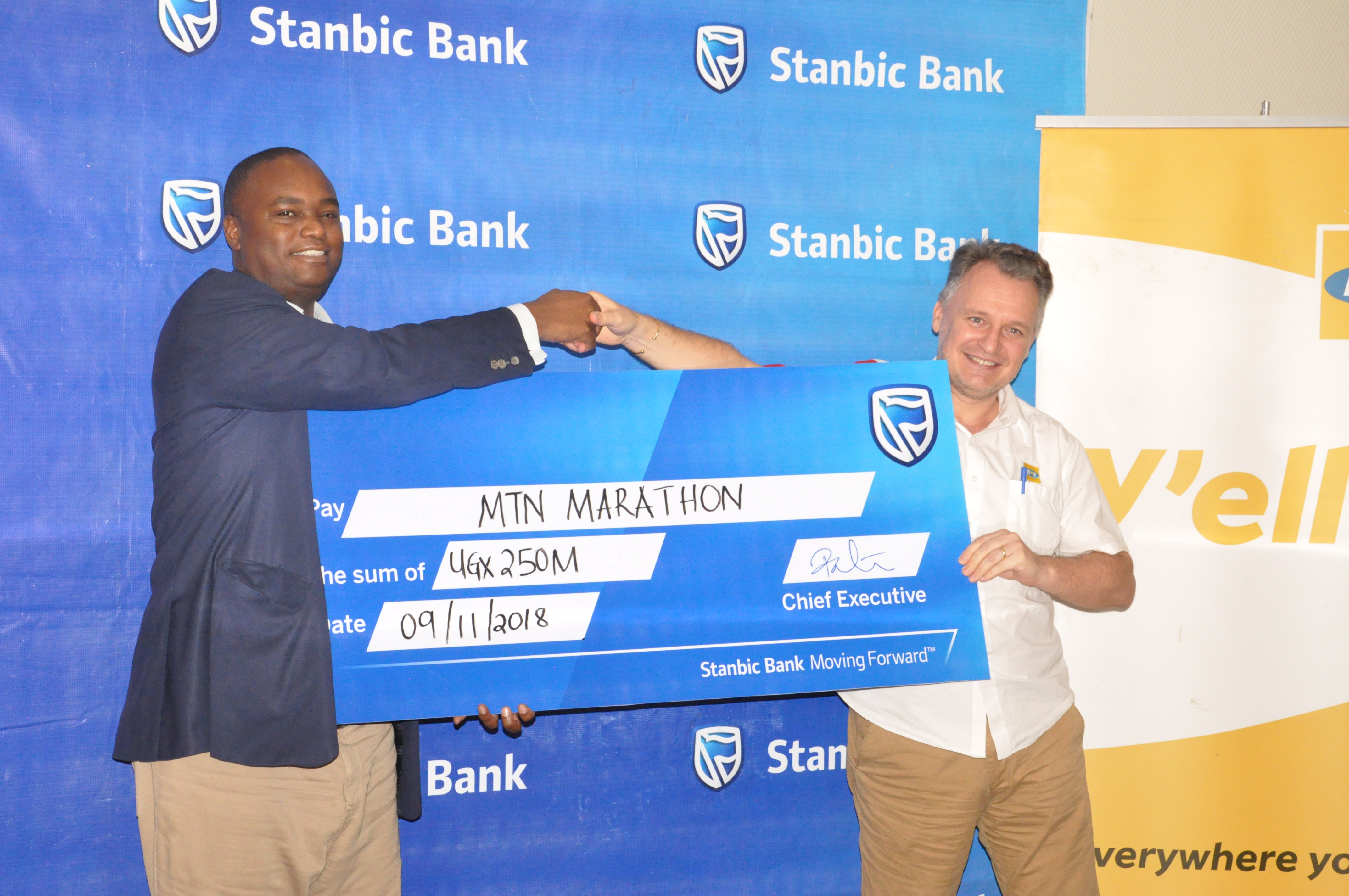 Patrick Mweheire, Stanbic Bank's CEO (L) hands over the banks contribution of UGX250M to MTN Uganda's CEO Mr. WimVanhelleputte. The contribution goes towards improving maternal health in Uganda.