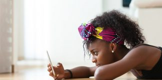 African American woman sending a text message on a mobile phone - Black people. (Photo Courtesy)