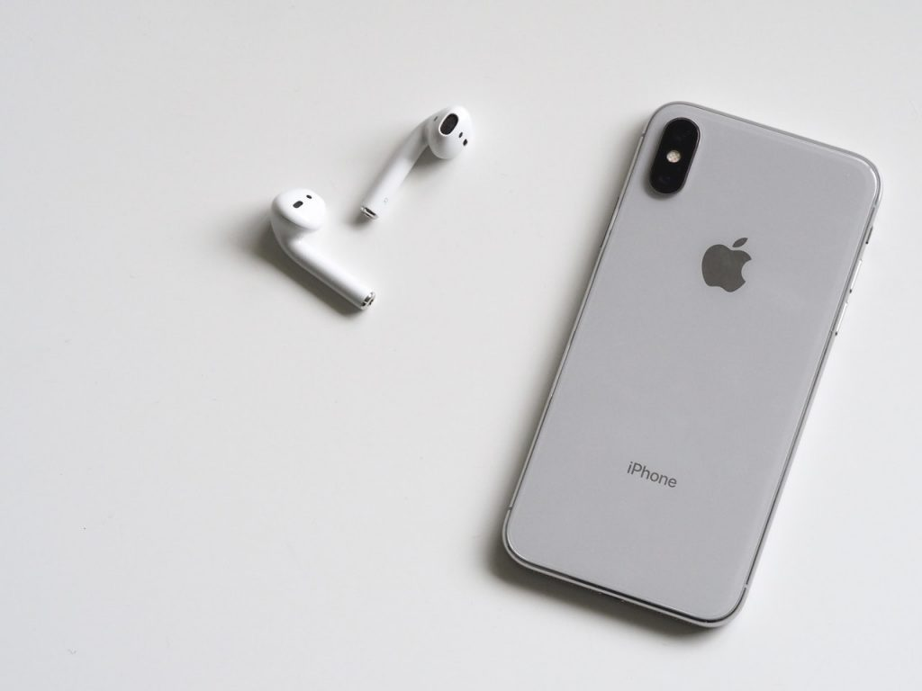 A Pair of Apple's AirPods pictured next to an iPhone. (Photo by Plush Design Studio from Pexels)