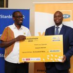 MTN Uganda's Senior Manager, Brand and Communications; Martin Sebuliba (L) and Stanbic Bank Uganda Chief Executive Officer; Patrick Mweheire (R) pictured holding a dummy thank you card showing the amount of money collected (UGX600M) from the MTN 2018 marathon.