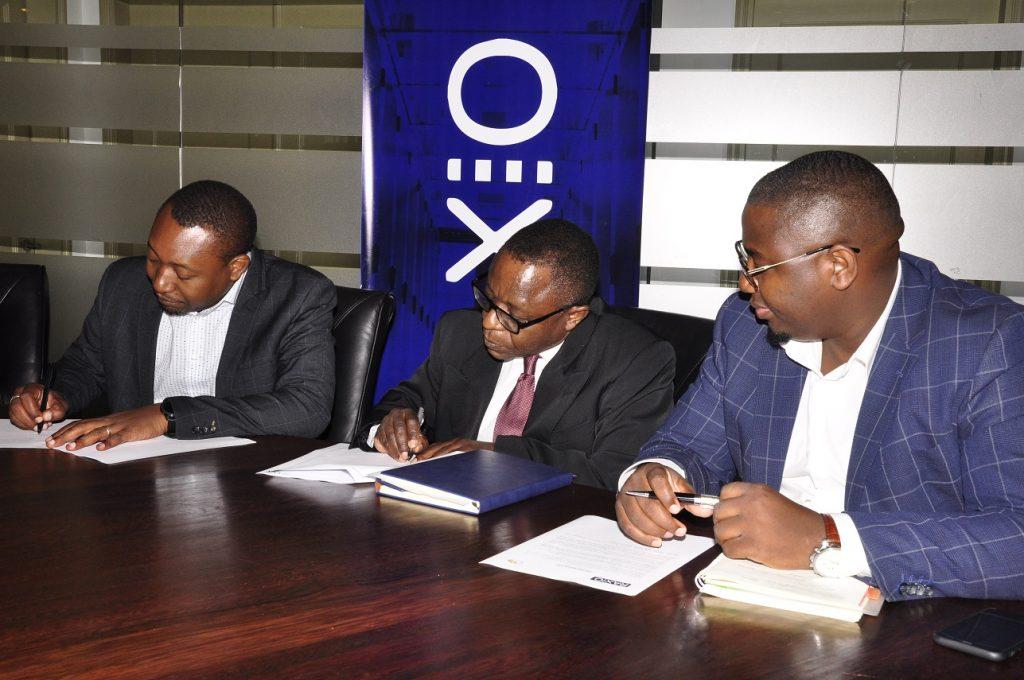 (Left –Right) Raxio's General Manager James Byaruhanga, Paul Nalikka, Director, Hamilton Telecom, flanked by Ahura Vianne Allan the CFO sign a service level agreement at Raxio's offices at Rwenzori Towers, in Nakasero, Kampala.