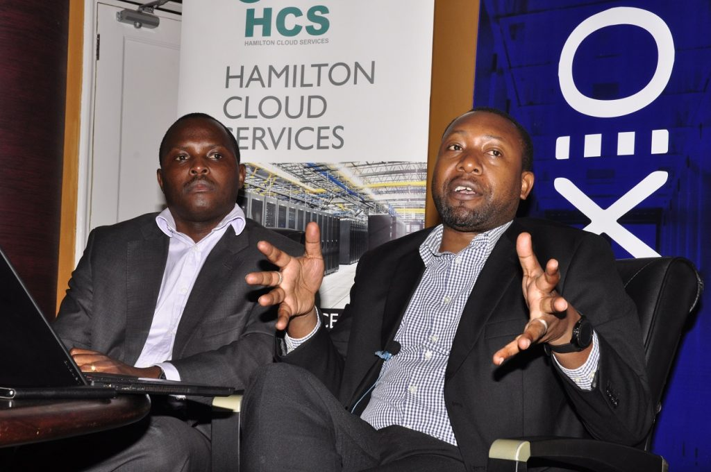 Raxio's General Manager James Byaruhanga (R), addressing the press after the signing of the service level agreement at Raxio's offices at Rwenzori Towers, in Nakasero, Kampala while Hamilton Telecom Chief Operating Officer, Derrick Sebbaale (L) looks on.