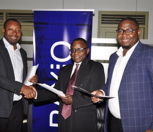 (Left –Right) Raxio's General Manager James Byaruhanga, Paul Nalikka; Director at Hamilton Telecom, flanked by Ahura Vianne Allan the CFO exchange agreements at Raxio's Rwenzori Towers, offices in Nakasero, Kampala.