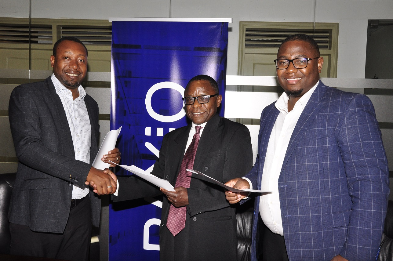 (Left –Right) Raxio's General Manager James Byaruhanga, Paul Nalikka, Director, Hamilton Telecom, flanked by Ahura Vianne Allan the CFO sign a service level agreement at Raxio's offices at Rwenzori Towers, in Nakasero, Kampala.
