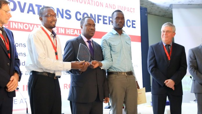 Hon. Elioda Tumwesigye, Minister of Science Technology and Innovation (center) giving out an award to one of the winners at the first Health Innovation Conference in March 2018 | File Photo/UAHII.