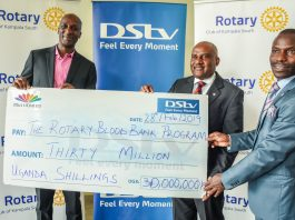 Charles Hamya, MultiChoice Uganda GM (L) handing over a UGX30 million dummy cheque to Chairman of Rotary Blood Bank Program, Emmanuel Katongole (center) and Timothy Basiima, Treasurer at Blood Bank Program (R) during a press media brief held at the MultiChoice Uganda head offices in Kololo on Wednesday 27th, February 2019.