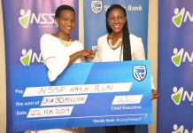 NSSF Head of Marketing and Communications, Ms Barbara Arimi (L) receiving a dummy UGX30 million cheque from Adengo Cathy, Stanbic Bank Uganda Head of Corporate Communications at a press briefing that was held at Crested Towers, Stanbic Bank Uganda Head offices on Friday 22nd, February 2019.