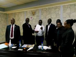 Sam Rwakoojo, Secretary of the Electoral Commission hands over a copy of the General Elections Roadmap for 2020/2021 to Giles Muhame, President of the OMPA.