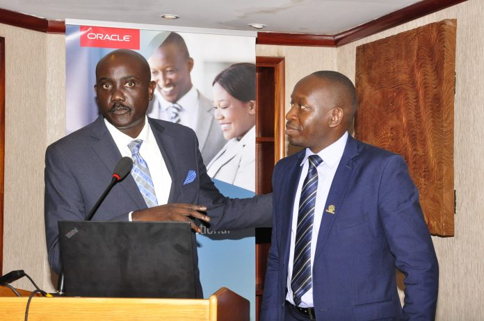 Dr. Tumubweine Twinemanzi, the Executive Director Supervision, at Bank of Uganda (BoU) (L) and Oracle's Byron Osiro, the Oracle Senior Cloud Platform Manager, East Africa (R) during the first Oracle-Raxio executive roundtable event at Serena Kampala Hotel, on March 6th 2019