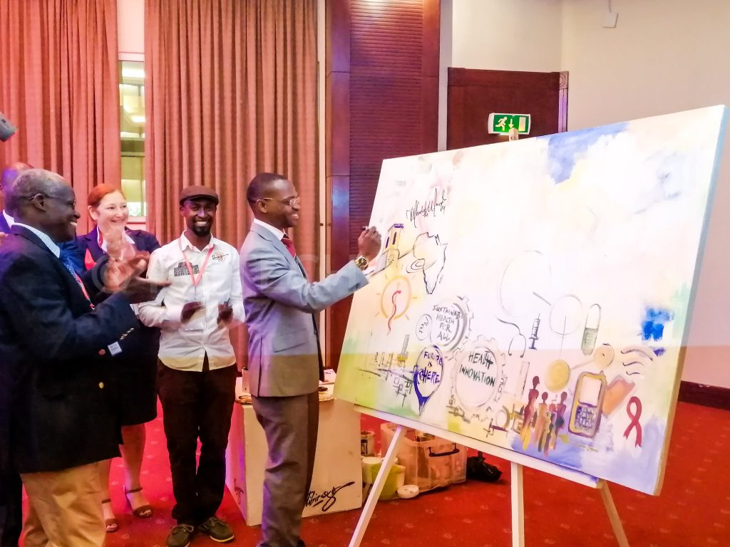 Dr. Umar Kakumba signing on a commemorative painting by renowned live events artist Ronald Tibirusga at the opening ceremony of the Health Innovation Conference at the Kampala Serena Hotel on Tuesday 19th, March 2019 | Photo by PC TECH MAGAZINE/Olupot Nathan Ernest.