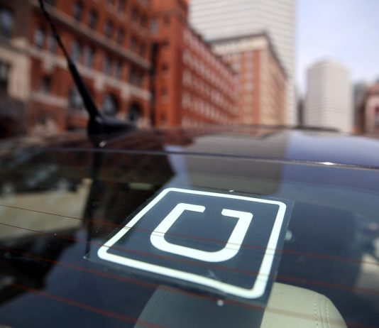 The Uber logo is displayed on the window of a vehicle | File Photo/Curbed Boston via Getty Images.