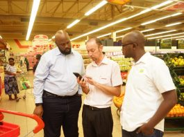 Steven Nsubuga (L) Segment Manager Mobile Financial Services at MTN Uganda and Isaac Tegule; Brand & Communications Marketing Manager (right) watch keenly as Jayte Slabbert, Shoprite Uganda General Manager demonstrates how to use Momopay.