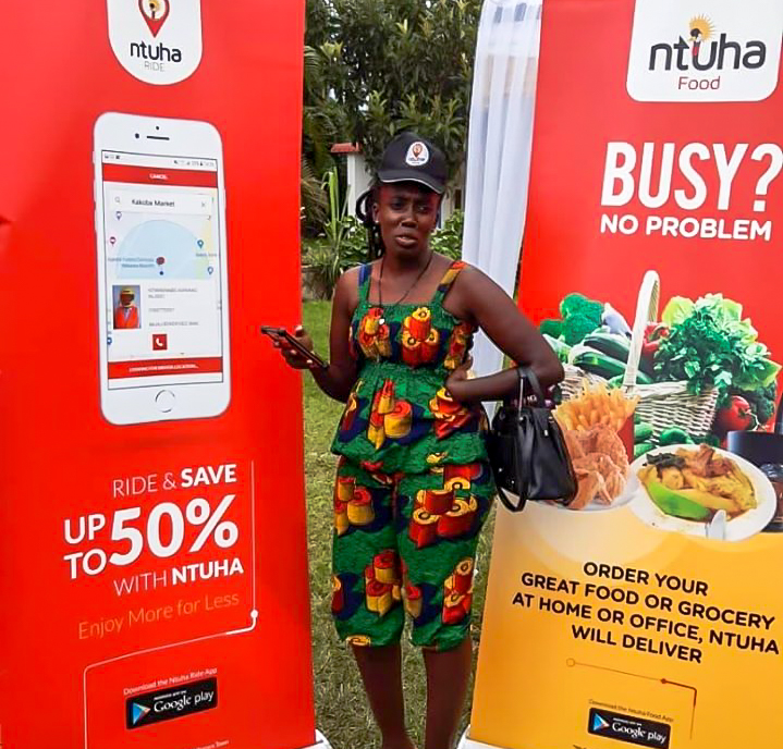 Ntuha offering both delivery and hailing services. Pictured a lady stands between the companies banners at an expo in Mbarara.